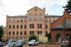 Rückseite vom Carl-Ritter-Haus, ehem. Gymnasium in Quedlinburg. Rundbogenfenster - Backsteingebäude mit eingefärbten gelben Streifen.