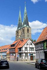 Fachwerkhäuser und Kirchtürme der St. Nikolai Kirche in Quedlinburg; blauer Himmel, weiße Wolken.