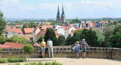 Touristen blicken vom Schlossberg auf die Dächer der Welterbestadt Quedlinburg - Hausdächer und Kirchtürm der St. Nikolaikirche.