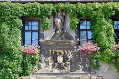 Eingang vom Quedlinburger Rathaus, die Fassade ist mit Kletterpflanzen bewachsen - das zweigeschossige gotische Gebäude ist eines der ältesten Rathäuser Mitteldeutschlands. Über dem Eingangsportal befindet sich als Brustschild eines schwarzen Rei