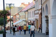 Strasse mit Aussenrestaurant, Café in Kutná Hora / Kuttenberg; Blumendekoration an den Laternenmasten.