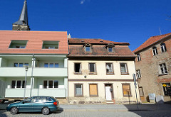 Neu + Alt - Wohnhäuser in Aschersleben; Neubau mit Balkons und ausgebautem Dach, mintgrün gestrichene Hausfassade; daneben eine leerstehende Hausruine mit vernagelten Fenstern.