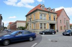 Strassenverkehr in Aschersleben - Strassenkreuzung; Grunderzeitgebäude mit gelben Ziegeln, Fassadenaufschrift Samen Handlung; im Hintergrund die WEMA Halle.