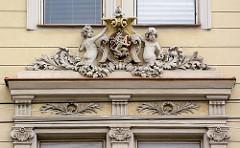 Architektur der Stadt Hradec Králové / Königgrätz - Arkanthusdekor im Fenstersturz, Putten halten das Wappen der Stadt - stehender Löwe mit G.
