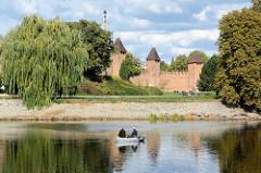 Blick über die Elbe zur alten Stadtbefestigung in Nymburk / Neuenburg; Schlauchboot mit Angler auf dem Wasser.