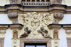 Dekorelemente am Eingang des Bischofspalasts in Hradec Králové / Königgrätz; Putten und Engelsfiguren, Engel mit Flügel - eine Figur hält ein Tableau mit der lateinischen Gruß- und Segensformel AVE.