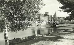 Historisches Bild, Schuten Holzboote liegen am Elbufer - Blick über die Elbe zum Ostböhmisches Museum in Hradec Králové / Königgrätz - Entwurf des Architekten Jan Kotěra, moderne tschechischen Architektur, fertig gestellt 1912; Figurenschmuck V