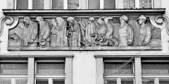 Relief an einem Gebäude in Dvůr Králové nad Labem / Königinhof an der Elbe. Männer und Frauen mit Kind werden von dem personifizierten Tod mit Drachen vor sich her getrieben - dahinter Soldaten, die zusehen. Signatur Antonia Mara, 1924.