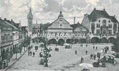 Historische Aufnahme vom Marktplatz in Dvůr Králové nad Labem / Königinhof an der Elbe; Blick auf das Rathaus - auf dem Platz sind Marktstände aufgebaut, Passanten schlendern auf der Strasse. Im Hintergrund die ehem. romanische Dekanatskirche Joh