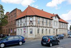 Verkehrsstraße in Aschersleben - Geschwister Scholl Strasse; Gebäude mit Fachwerk-Stockwerk; daneben Industriearchitektur, Backsteinfassade.