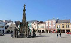 Mariensäule mit Heiligenfiguren - im Hintergrund unterschiedliche Architekturstile am Marktplatz von Dvůr Králové nad Labem / Königinhof an der Elbe.