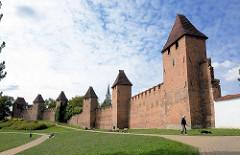 Historische Stadtbefestigung in  Nymburk / Neuenburg an der Elbe in Tschechien; Stadtmauer mit Wehrtürmen - Spaziergänger mit Hund.