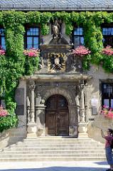 Eingang vom Quedlinburger Rathaus, die Fassade ist mit Kletterpflanzen bewachsen - das zweigeschossige gotische Gebäude ist eines der ältesten Rathäuser Mitteldeutschlands. Das Eingangsportal ist von Säulen gerahmt - über dem Portal befindet sich