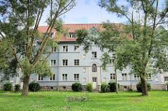 Mehrgeschossiger Wohnblock am Heinrichplatz in Quedlinburg; hellblaue Fassade - Grünanlage.