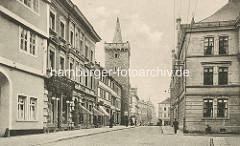 Alte Aufnahme - Geschäftsstrasse / Breite Straße  in Aschersleben - Geschäfte mit Markisen, Blick zu einem Stadtturm der historischen Stadtbefestigung.
