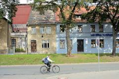 Schlichte einstöckige Wohnhäuser - farbige Fassade, grauer Putz - Radfahrer / Bilder aus Aschersleben.