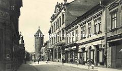 Historische Straßenansicht der Straße Havlíčkova in Dvůr Králové nad Labem / Königinhof an der Elbe - Kinder spielen auf der Strasse, Geschäftsinhaber stehen in der Ladentür; im Hintergrund ein alter Wehrturm der ehem. Stadtbefestigung.