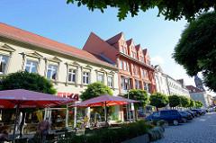 Wohn- und Geschäftshäuser am Marktplatz von Aschersleben - Café auf der Strasse mit Sonnenschirmen.