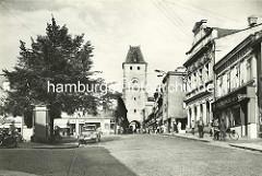 Historische Aufnahme vom Prager Tor in Mělník  - Passanten auf dem Bürgersteig, parkendes Auto.
