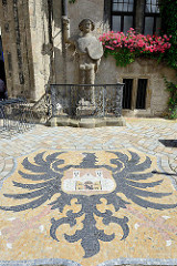 Wappen von Quedlinburg als Mosaik im Boden vor dem Rathaus eingelassen, dahinter der Quedlinburger Roland, der neben dem Roland von Bremen und Halberstadt eine der ältesten Rolandfiguren ist.