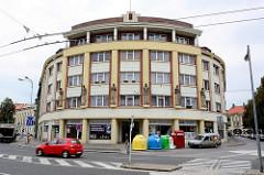 Rundes Eckhaus - Art Deko Fassade mit Figurenschmuck, Geschäfte im Erdgeschoss; Wohnblock in Hradec Králové / Königgrätz.