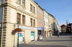 Wohn- und Geschäftshäuser - historische Gebäude, Geschäfte im Erdgeschoss - im Hintergrund die Mariensäule in Kutná Hora / Kuttenberg.