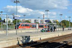Bahnhof von Aschersleben - Regionalzug und wartende Fahrgäste, im Hintergrund ein Hochhaus / Wohnblock mit farbigen Balkons.