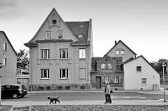 Wohnhäuser in Aschersleben - unterschiedliche Baustile und Hausgrößen; Spaziergänger mit Hund - Schwarz Weiß Bild.