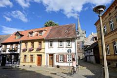 Wohnhäuser an der Kaiserstrasse in Quedlinburg - im Hintergrund der alte Wehrturm Kuhhirtenturm / Turm opm Tittenplan; mittelalterlicher Wehrturm, Teil der ehem. Stadtbefestigung.