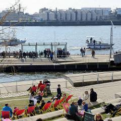 Frühlingssonne in der Hansestadt Hamburg - Promenade am Grasbookhafen; Besucher der Hamburger Hafencity sitzen auf den Dalmannkai Treppen und Liegestühlen in der Sonne. Im Hintergrund die Norderelbe und der Fähranleger Elbphilharmonie.