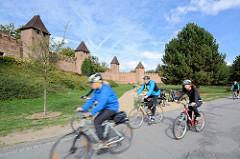 Historische Stadtbefestigung in  Nymburk / Neuenburg an der Elbe in Tschechien; Stadtmauer mit Wehrtürmen - Radfahrer mit Helmen, Fahrradtour an der Elbe.