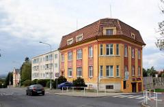 Gründerzeit Mietshaus mit farbiger Fassade, schlichter Neubau mit Balkons, Architektur in Mělník.