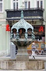 Hennebrunnen in Aschersleben; die Brunnenanlage zeigt eine durch einen Baldachin überdachte gegliederte Säule, auf der acht eigenartige Bronzeputten sitzen. Der Brunnen wurde von Georg Wrba entworfen und 1906 eingeweiht.