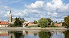 Blick über die Elbe zur alten Stadtbefestigung in Nymburk / Neuenburg; Schlauchboot mit Angler auf dem Wasser; lks. die St. Ägidius Kirche.