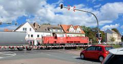 Bahnübergang in Aschersleben; die Schranken sind herunter gelassen, ein Güterzug mit Lokomotive / Lok 251 019-4 der Deutschen Bahn kreuzt die Strasse - wartende Autos.