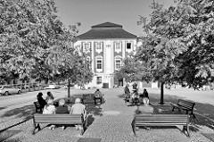 Ruhebänke im Schatten unter Bäumen - Platz mit Pflastersteinen in Kutná Hora / Kuttenberg.