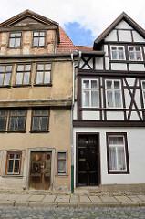 Alt + Neu, Fachwerkhäuser in Quelinburg - re. restauriert mit gestrichener Fassade - lks. grauer Rauputz und abblätternde Farbe / leerstehendes Gebäude.
