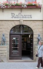 Marktseite vom Rathaus in Aschersleben - Eingang mit Schriftzug und Bronzeskulpturen.