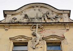 Hausfassade, abbröckelnder Putz in der Straße Havlíčkova in Dvůr Králové nad Labem / Königinhof an der Elbe - ehem. Grand Hotel; betrunkene / trunkene Putten die an der Weinpresse arbeiten - in erotischer Umarmung oder schlafend in der Eck