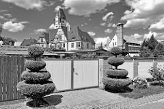 Mauer mit Tor - in Stufen geschnitter, runder Buchsbaum - im Hintergrund das Gutshaus an der Wiperitstrasse in Quedlinburg; erbaut um 1900, Architekt Max Schneck - Baustil des Späthistorismus.