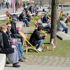 Frühlingssonne in der Hansestadt Hamburg - Promenade am Grasbookhafen; Besucher der Hamburger Hafencity sitzen auf den Dalmannkai Treppen und Liegestühlen in der Sonne.