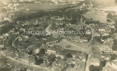 Historische Luftaufnahme von Nymburk / Neuenburg an der Elbe in Tschechien; in der Bildmitte der Marktplatz der Stadt, dahinter die Kirche und das Wasserwerk.