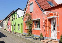 Einzelhäuser mit geschlossener Strassenfront in der Pohlstraße von Barth - orangerot oder mintgrün gestrichene Hausfassaden.