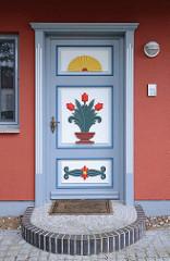 Tür mit farbigen Dekorelementen - Schnitzerei; Tulpen und aufgehende Sonne - im Ostseebad Zingst, Mecklenburg-Vorpommern.