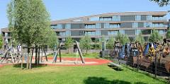 Neubauquartier, sogen. Marina auf der Schlossinsel im Harburger Hafen - Kinderspielplatz; re. abmontierte Baggerschaufel hinter einem Zaun.