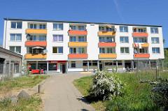 Sanierter Wohnblock mit bunten Balkonfassaden - Korrallusstraße in Hamburg Wilhelmsburg; Bauzaun und Wildkraut.