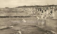 Historisches Foto vom  Ostseebad Zingst - Badegäste am Wasser; Kinder / Mädchen in Kleidern mit den Füssen im Wasser - Frauen in langen Kleidern mit Hüten am Strand.