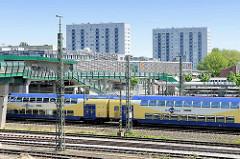 Blick über die Zuggleise an der Haltestelle Hamburg Wilhelmsburg; ein Metronomzug fährt Richtung Hauptbahnhof; im Hintergrund der Busbahnhof  Hochhäuser.