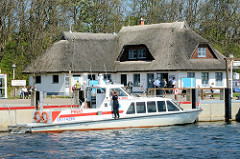Hafenanlage von Kloster auf der Ostseeinsel Hiddensee - Wassertaxi; reetgedecktes Haus vom  Hafenmeister.