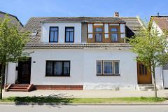 Doppelhaus in der Bergstraße von Ribnitz-Damgarten; eine Hälfte restauriert, mit neuen Fenstern - die andere Hälfte renovierungsbedürftig, mit freigelegtem Fachwerk.